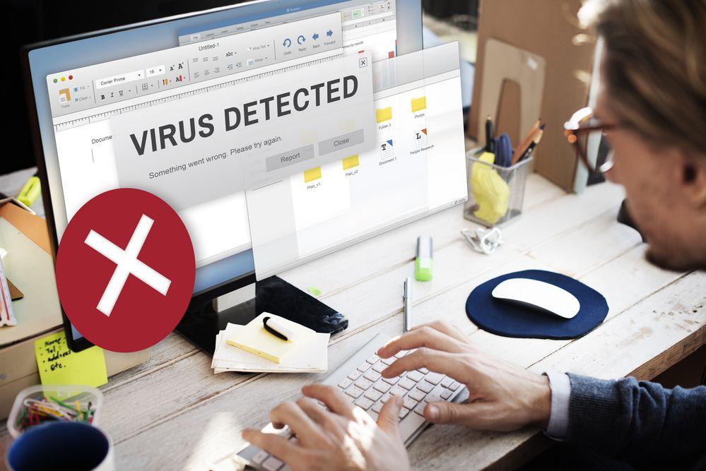 Homem usando um computador com uma mensagem na tela alertando sobre a detecção de vírus
