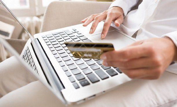 Mulher sentada no sofá usando um notebook com a mão direita e segurando um cartão de crédito com a mão esquerda